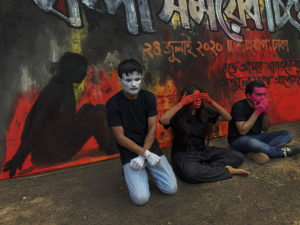 Artists protest against Digital Security Act 7980 at Shahbag square in Dhaka, Bangladesh. Three people are sitting in front of a wall with paintings and graffiti. All of them have coloured their faces and hands in paint. The first person has his hands cuffed, the second one is closing their eyes with their hands, the third one it closing his mouth with his hands.