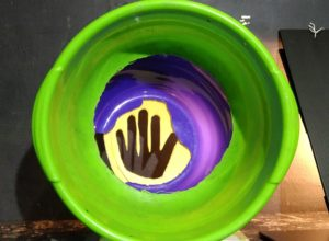A green ceramic pot from above, on the bottom on purple and yellow a black hand-like symbol.