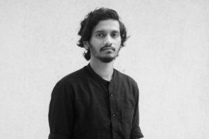 Ein schwarz-weiß Foto des Künstlers. Er schaut neutral bis ernst in die Kamera, hat dichtes dunkles Harr, etwas Bart und trägt ein dunkles Baumwollhemd.