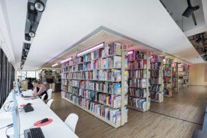Ein Foto aus der Asia Art Archive Library. In der Mitte befinden sich Regale mit Büchern und am linken Bildrand sitzt eine Besucher*in am Computer.