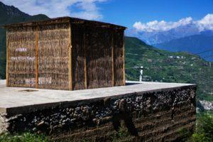 Eine Bambushütte auf einem Dach eines Gebäudes. Im Hintergrund ein Wohngebiet in einer bergig, grünen Landschaft.