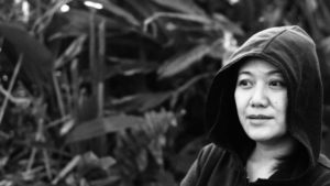 A black and white photo of the artist. She has a hood on and looks into the distance.