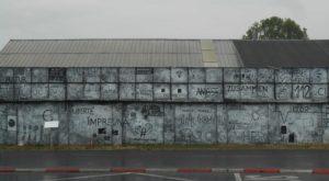 Ein Gebäude, die Außenwand ist mit weißen und schwarzen Permanentmarker bemalt. Es sind verschiedene Begriffe und Malereien zu sehen.