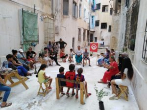 Residents and children sit in a circle in a courtyard and talk to each other. The Tunisian flag hangs on a clothesline above them.