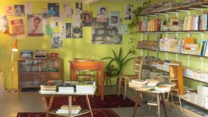 Ein Zimmer möbliert im 60er Jahre Stil, mit grünen, plakatierten Wänden und einem großen Bücherregal. In der Mitte auf kleinen Tischen liegen weitere Stapel Bücher. Hinten auf der Wandkomode ein Radio, eine Schreibmaschine und ein Telefon.