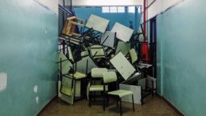 Chaotisch aufeinander gestapelte Schultische und Stühle am Ende eines blauen Flures.