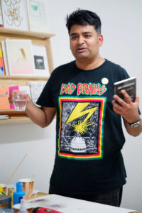 Hamja Ahsan with a glass and book in his hand.