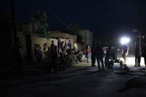 It is night and a film scene is being shot outdoors. Spotlights illuminate the camera team. Children and residents stand or sit along a wall and watch the filming.