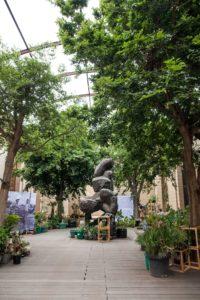 Installationsansicht. In der Bildmitte befindet sich eine Skulptur, sie wird umringt von Bäumen und Infotafeln.