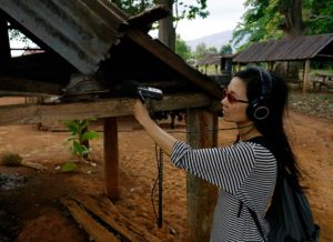 The artist, wearing sunglasses and headphones, holds a recording device in her outstretched hand. In the background village wooden huts.