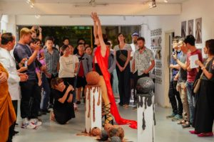 A group of visitors stand in the exhibition space and look at a man standing in the middle. He is wearing a long red vest and black laced high-heeled sandals and is stretching his arms upwards. In the foreground are two round sculptures on two pedestals. Some of the spectators take photos or videos with their cell phones.