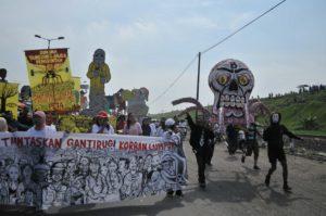 Karneval zum Gedenken an die Schlammtragödie von Lapindo vor 4 Jahren in Siring Barat. Menschen ziehen mit Kostümen und Pannern über die Straße.