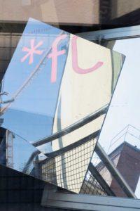 In einem Spiegel, der auf einem Fenster liegt spiegeln sich ein Gebäude, Teile eines Krahns und eines Zauns, blauer Himmel und die Anfangsbuchstaben des Kollektivnamens.