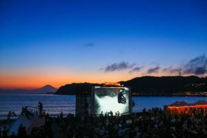 A film screening on a big screen on the beach at night with a lot of viewers