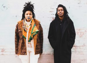 The two artists of Black Quantum Futurism stand in front of a white wall.