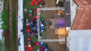A bird's eye view directly from above of an open air stage next to a building. The stage is framed by a white scaffolding. Two people are standing on the stage. In front of the stage red chairs, some empty, some with visitors.