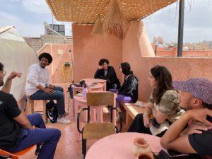 Menschen sitzen auf einer Dachterrasse und nehmen an einem Künstler*innenworkshop teil